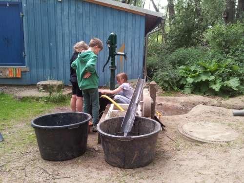 Abenteuerspielplatz Lernziel Spielen - Wasser wird an der Pumpe geholt