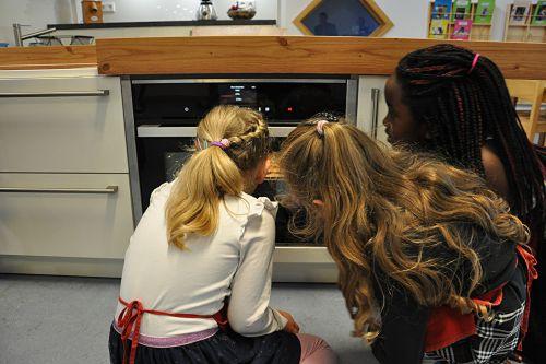 AWO Kinderkueche - Mädchen warten vor dem Backofen