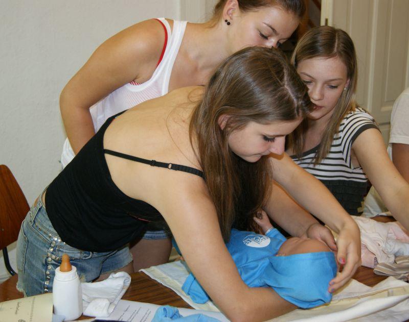 Schülerinnen üben den Umgang mit einem Neugeborenen