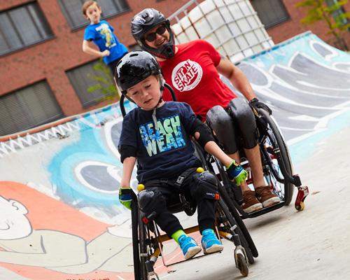 Zwei ROhllstuhlsportler mit Helm im Skatepark