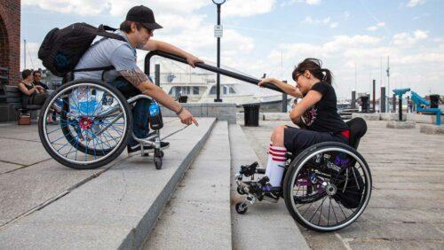 zwei Rollstuhlfahrer überwinden eine Treppe
