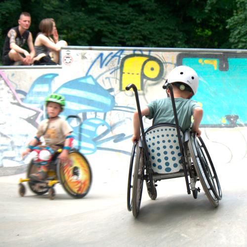 Zwei Jungs mit Helm im Rollstuhl fahren im Skatepark