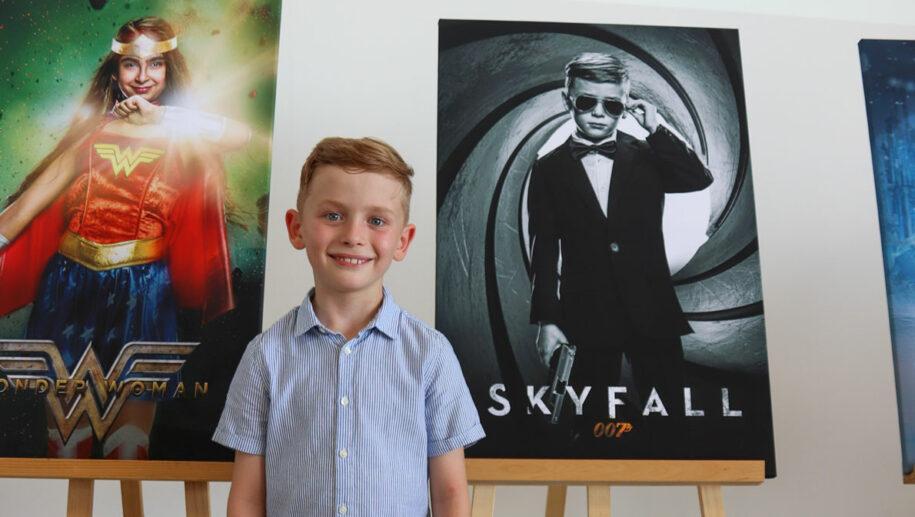 Junge vor seinem Superhelden-Poster